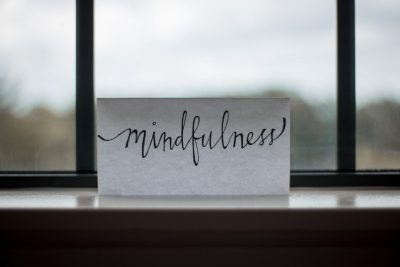 """card that reads """"mindfulness"""" on window"""
